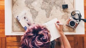 ragazza-carta geografica-penna-quaderno-guida di viaggio