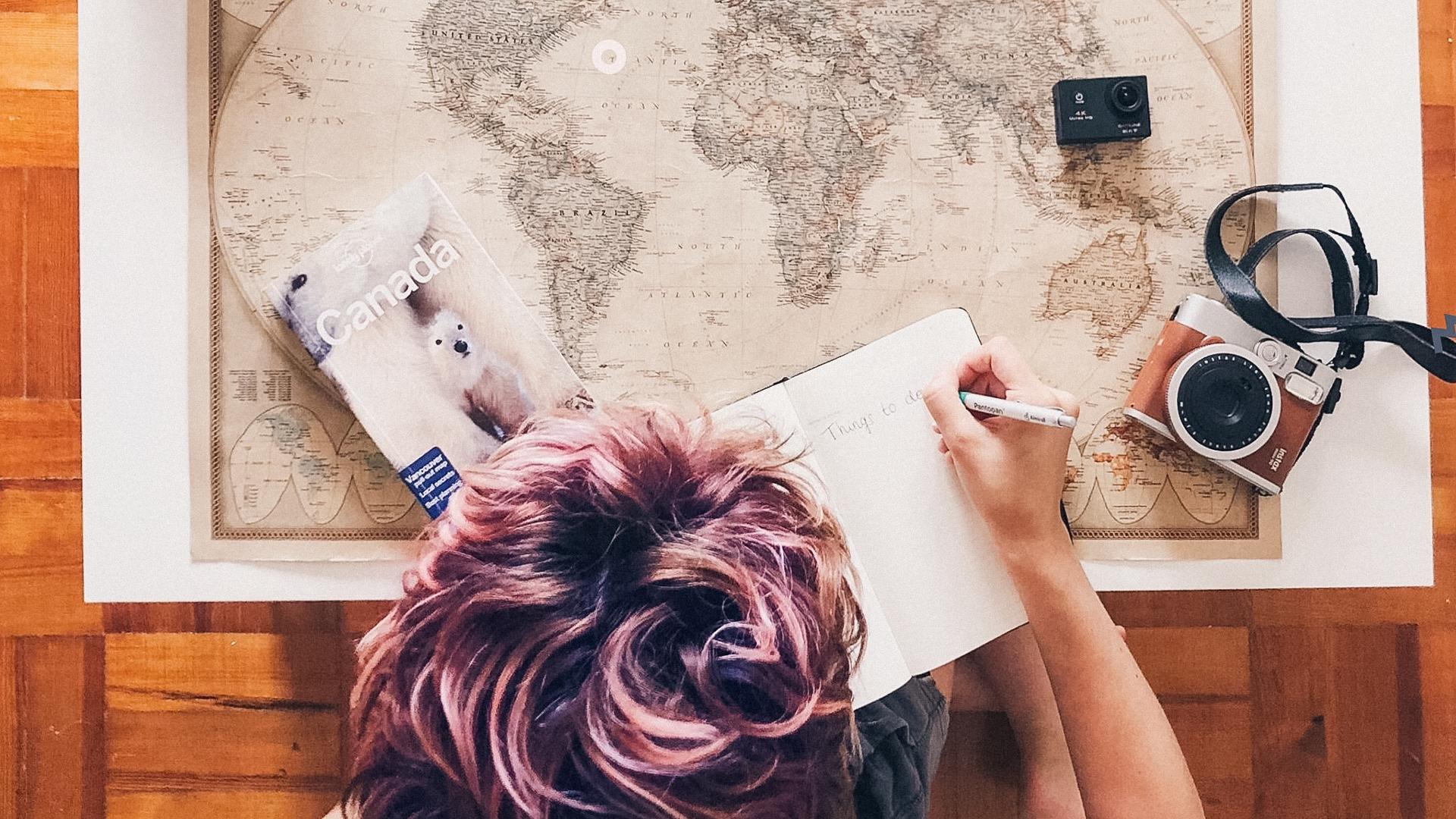 trasferirsi all'estero-ragazza-carta geografica-penna-quaderno-guida di viaggio