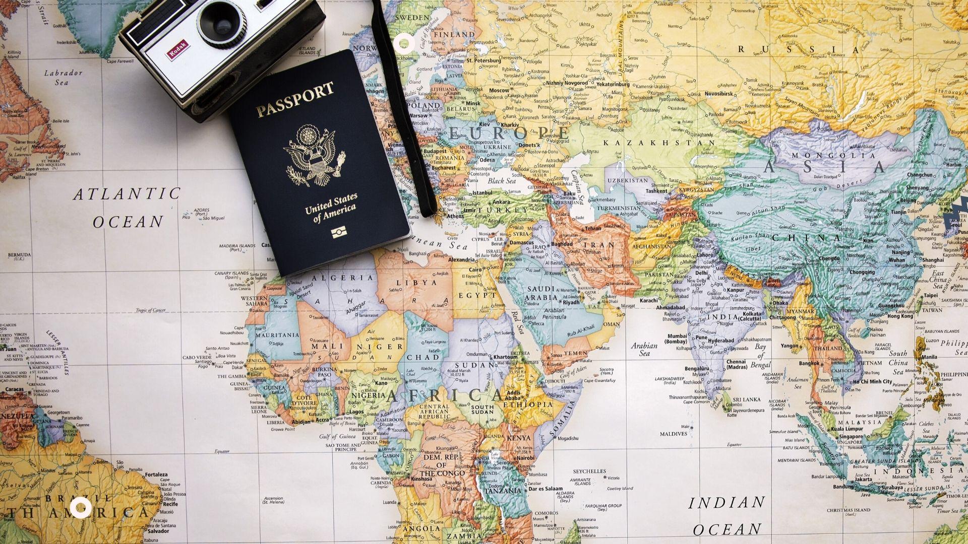 Trasferirsi all'estero-cartina geogarafica-passaporto-macchina fotografica