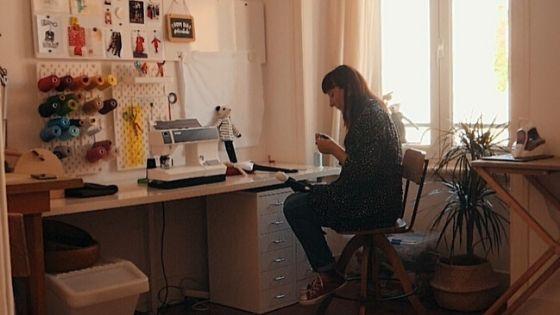 donna seduta alla scrivania con macchina da cucire