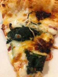 trancio di pizza con spinaci e mozzarella