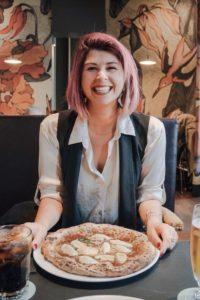 ragazza che ride mentre mangia una pizza margherita